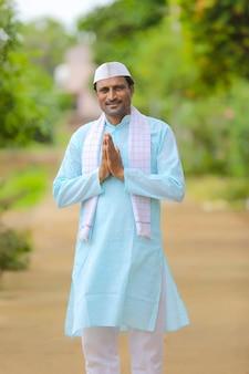 Giovane agricoltore indiano in abiti tradizionali e dando namaste o gesto di benvenuto