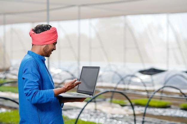 Giovane agricoltore indiano utilizzando laptop in serra o poli casa