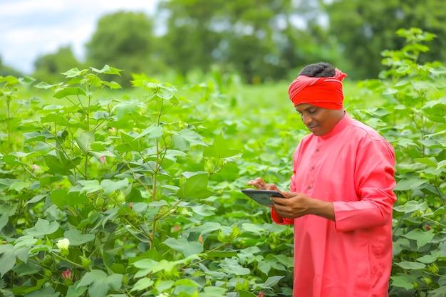 Giovane agricoltore indiano utilizzando il telefono cellulare al campo agricolo