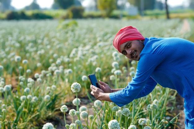 Giovane agricoltore indiano utilizza lo smartphone in campo agricolo