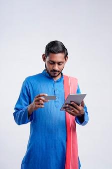 Giovane agricoltore indiano che utilizza smartphone e carta bancaria su sfondo bianco.
