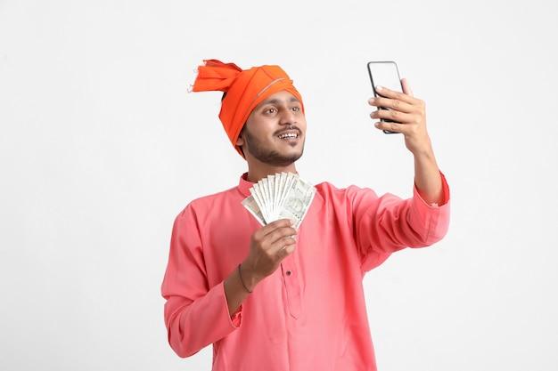 Giovane agricoltore indiano utilizza lo smartphone e mostra denaro su sfondo bianco.