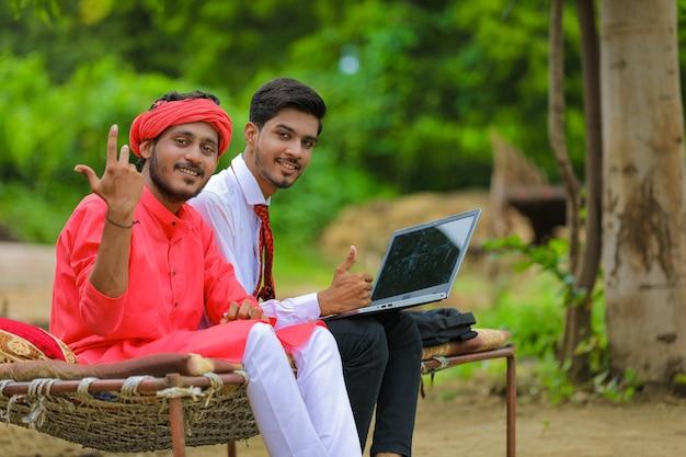 Giovane agricoltore indiano con agronomo o banchiere a casa