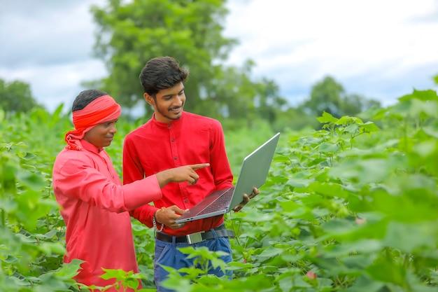 Giovane agricoltore indiano con agronomo al campo di cotone