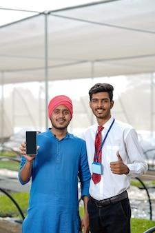 Giovane agricoltore indiano con agronomo che mostra smart phone in poli casa o serra