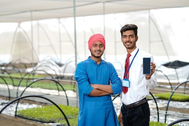 Giovane agricoltore indiano con agronomo che mostra smartphone in poli casa o serra