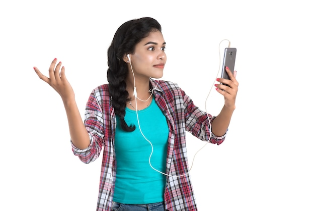 Giovane ragazza indiana utilizzando un telefono cellulare o uno smartphone isolato su un muro bianco