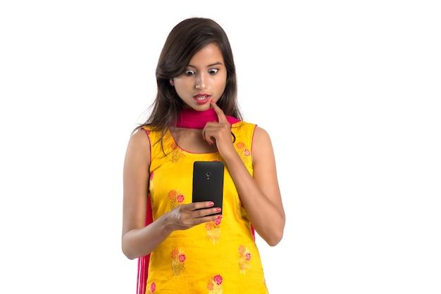 Giovane ragazza indiana utilizzando un telefono cellulare o uno smartphone isolato su un bianco