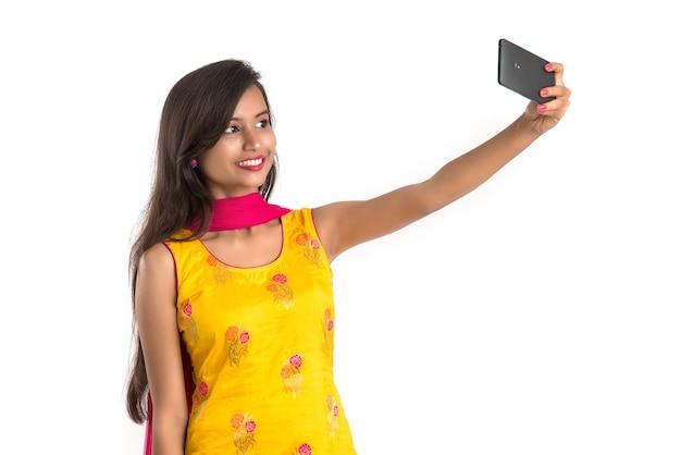 Giovane ragazza indiana utilizzando un tablet, un telefono cellulare o uno smartphone isolato su un bianco