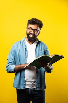 Giovane uomo indiano felice che indossa occhiali leggendo un libro e sorridendo isolato su giallo