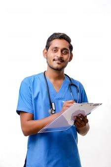 Il giovane medico maschio indiano si è vestito in uniforme con lo stetoscopio che prende le note in blocco note isolato sopra fondo bianco.