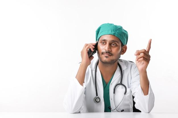 Giovane medico maschio indiano che parla sullo smartphone alla clinica