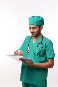 Giovane medico maschio indiano in uniforme con lo stetoscopio che prende le note in blocco note sopra fondo bianco.