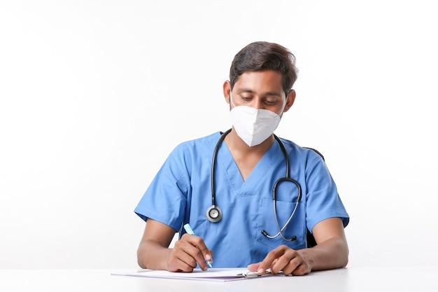Giovane medico maschio indiano che scrive sul blocco note alla clinica.
