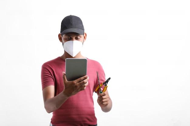 Il giovane tecnico o ingegnere maschio indiano ripara le apparecchiature elettroniche