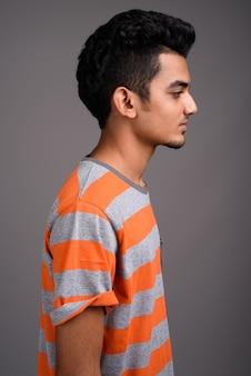 Giovane uomo indiano contro il muro grigio