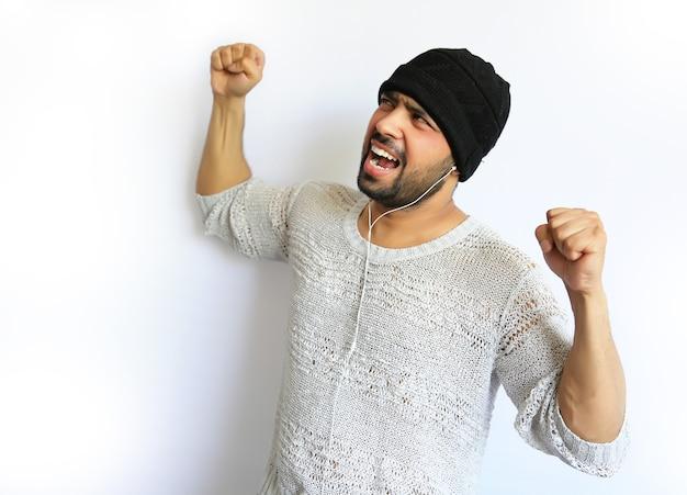 Giovane uomo indiano con un berretto nero che fa segno celebrativo e urla di grande eccitazione.
