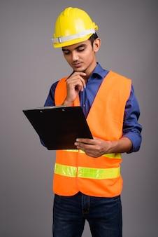 Giovane muratore indiano dell'uomo contro la parete grigia
