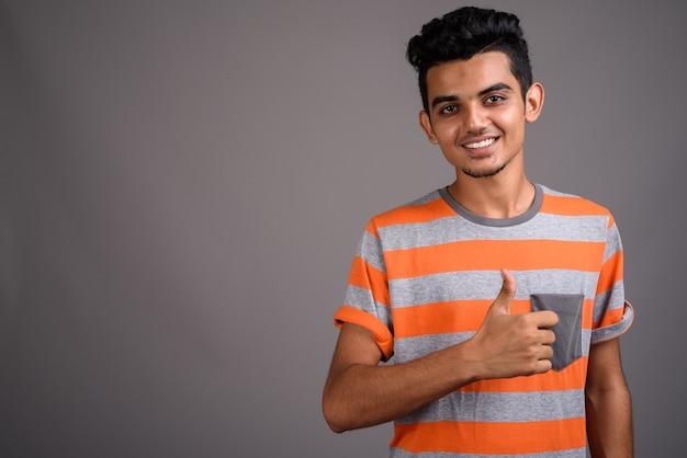 Giovane uomo indiano sul muro grigio