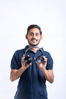 Giovane uomo indiano che ascolta musica e mostra espressione su sfondo bianco.