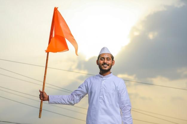 Giovane indiano (pellegrino) in abiti tradizionali e sventola bandiera religiosa.