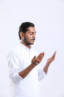 Giovane indiano che prega su sfondo bianco.
