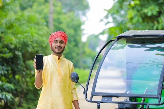 Giovane uomo indiano che mostra lo schermo del telefono con lo spazio della copia