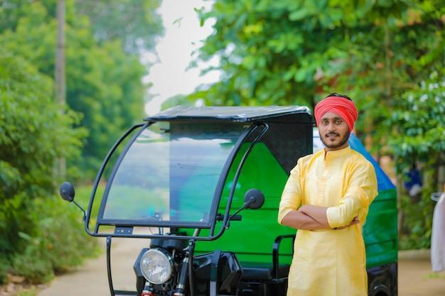 Giovane uomo indiano in piedi con il furgone della spazzatura