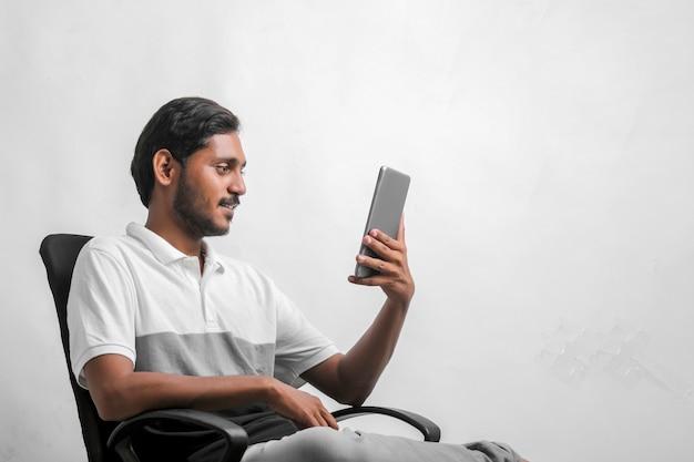 Giovane uomo indiano che utilizza compressa sopra fondo bianco.