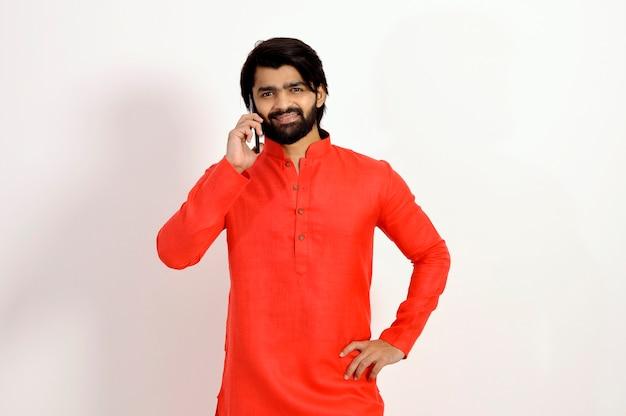 Giovane indiano che indossa kurta parlando su un telefono cellulare e sorridente