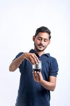 Giovane indiano che ripara utensili da cucina elettronici tenendo in mano gli strumenti