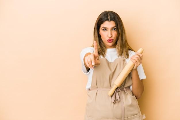 Giovane donna indiana del cuoco unico di pasticceria isolata che mostra il numero uno con il dito