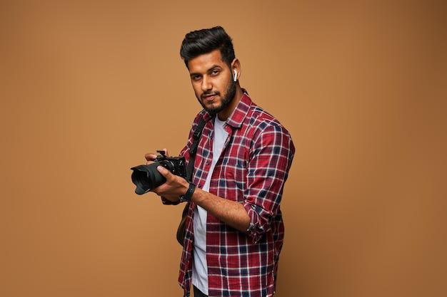 Giovane fotografo indiano con macchina fotografica nera professionale su muro pastello