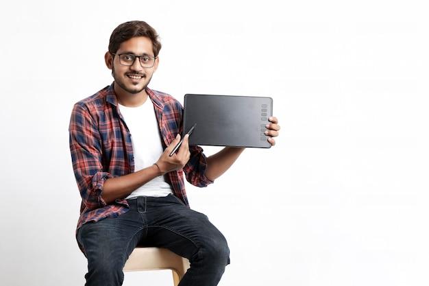 Giovane designer professionista indiano che mostra tavoletta grafica con penna digitale