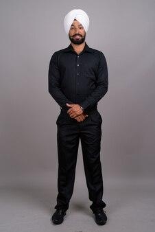 Giovane uomo d'affari indiano sikh che indossa turbante bianco