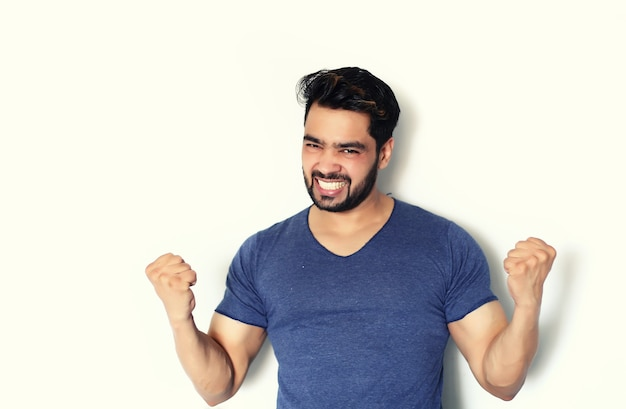 Giovane uomo indiano di successo che celebra con le braccia alzate isolato su bianco