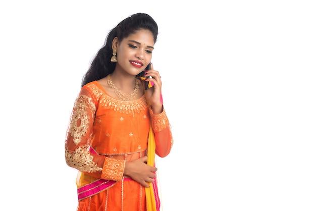 Giovane ragazza indiana tradizionale utilizzando un telefono cellulare o uno smartphone su bianco