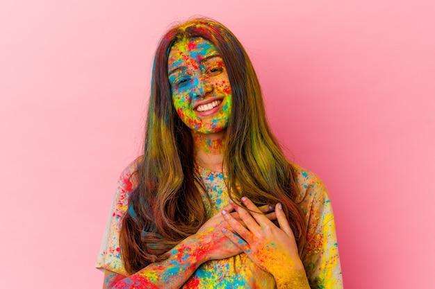 La giovane donna indiana che celebra la festa santa isolata su bianco ha un'espressione amichevole, premendo il palmo sul petto