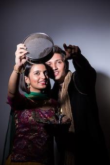 Giovane donna indiana che celebra il festival di karwa chauth con il marito