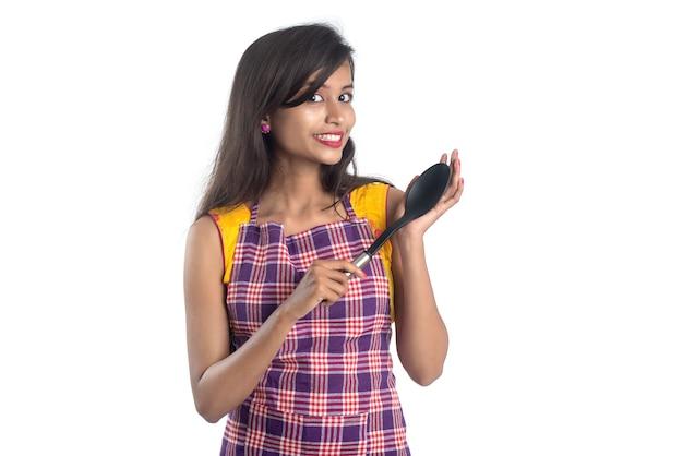Giovane donna indiana che tiene un utensile da cucina (cucchiaio, stapola, mestolo e padella, ecc.) su una parete bianca