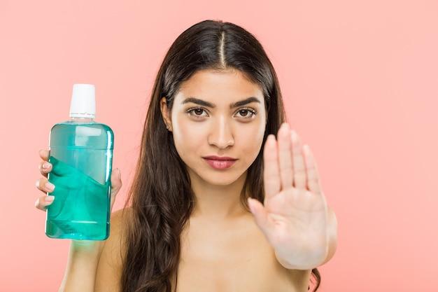 Giovane donna indiana che tiene una bottiglia di colluttorio in piedi con la mano tesa che mostra il segnale di stop, impedendoti.