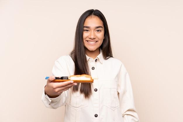 Sushi della holding della giovane donna indiana isolato sul beige con l'espressione felice