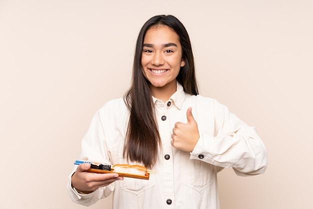 Sushi della holding della giovane donna indiana isolato sul beige con i pollici in su perché è accaduto qualcosa di buono