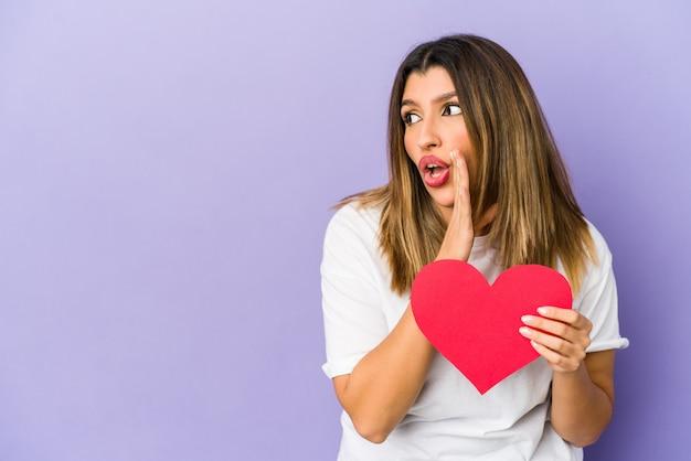 La giovane donna indiana che tiene un cuore di san valentino isolato sta dicendo una notizia di frenata calda segreta e sta guardando da parte