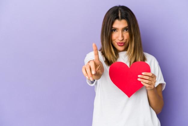 Giovane donna indiana che tiene un cuore di san valentino isolato che mostra il numero uno con il dito.