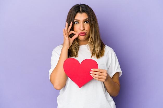 Giovane donna indiana che tiene un cuore di san valentino isolato con le dita sulle labbra mantenendo un segreto.
