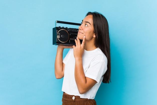 Giovane donna indiana che tiene un cassete dell'annata isolato