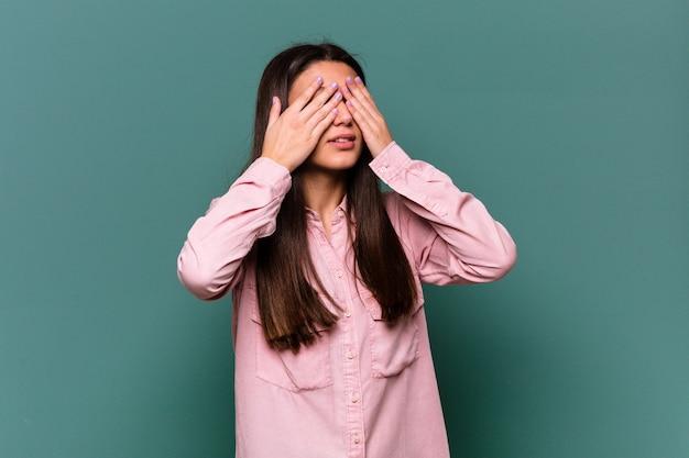 Giovane donna indiana isolata sul muro blu paura che copre gli occhi con le mani.