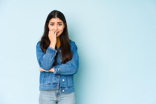 Giovane donna indiana isolata sulle unghie mordaci della parete blu, nervosa e molto ansiosa.
