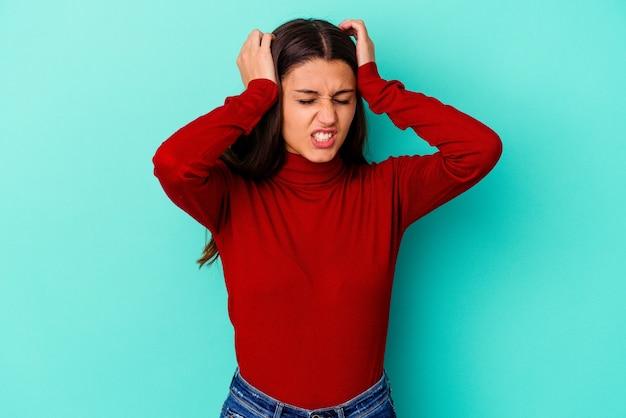Giovane donna indiana isolata sul muro blu che copre le orecchie con le mani.